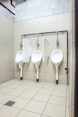 urinals in an old building for men only Stock Photo