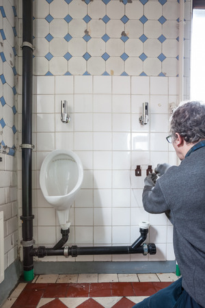 toilet: In an old building, the man is restoring the urinals