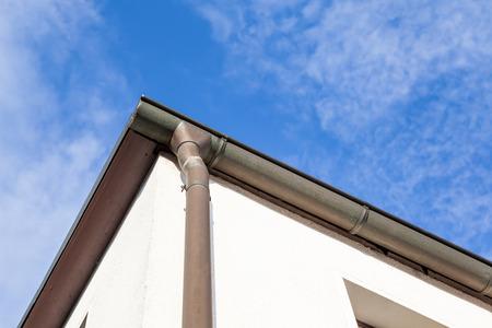 Ein Regen Abflussrohr vom Dach mit blauem Himmel und Wolken Standard-Bild - 85118106
