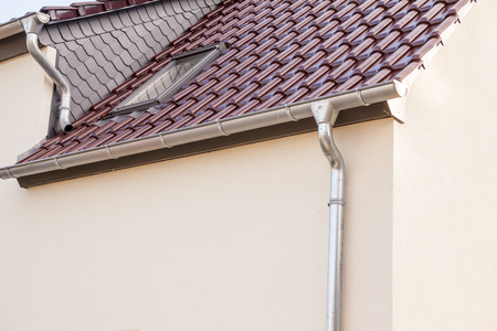 an rain drain pipe from the roof whit blue sky and clouds