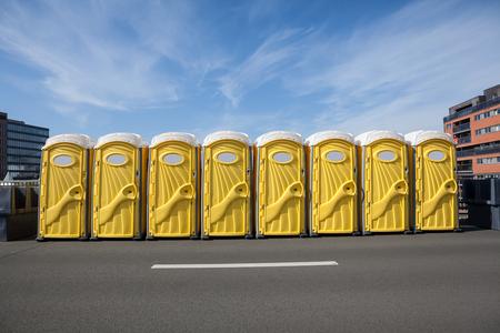 para actividades al aire libre hay baños amarillos a lo largo de la calle Foto de archivo