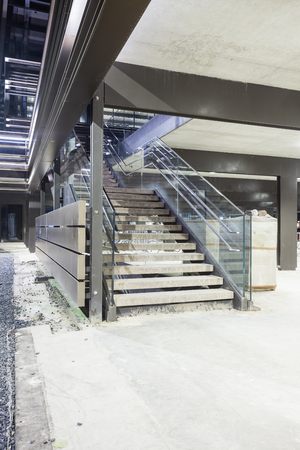 in a large building, there is a marble staircase whit glass handle