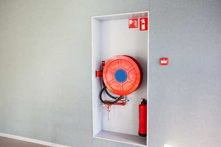 in the hallway of a nice building, there is a fire hose Foto de archivo