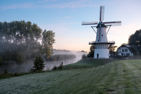 on the water there is an windmills in Deil in Holland on an froggy morning