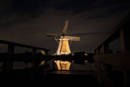 Beautiful windmills at Kinderdijk are illuminated with white light at the blue hour