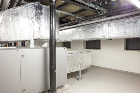 an long ventilation pipe in a technical room in the basement of a large building