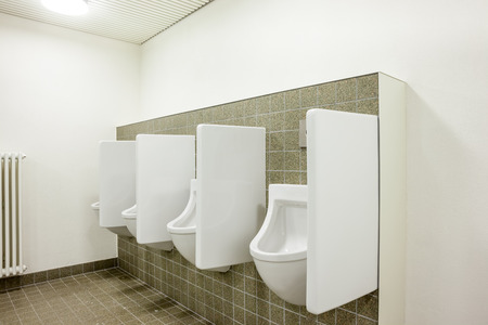 urinals in an old building for men only on the wall