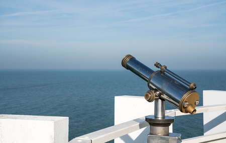 at the sea in a public place there is a public binocular