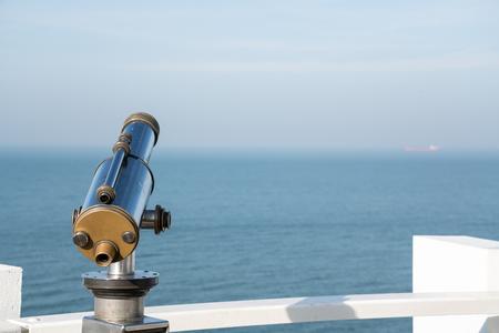 at the sea in a public place there is a public binocular Foto de archivo
