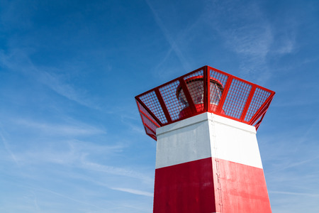 a red lighthouse with a beautiful blue sky on a beautiful day