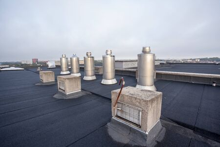 Five Chimney on the flat roof off a big building in the city Archivio Fotografico