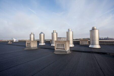 Quattro Camini sul tetto piano di un grande edificio in città Archivio Fotografico