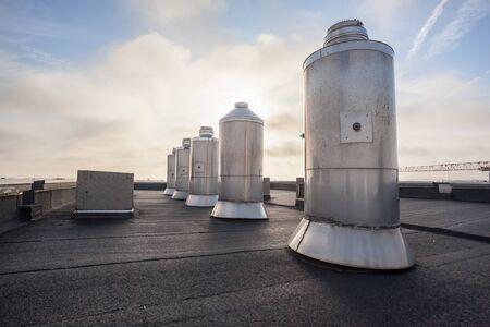 Fünf Schornsteine auf dem Flachdach eines großen Gebäudes in der Stadt