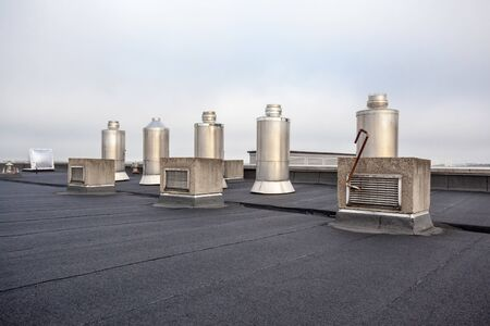 Five Chimney on the flat roof off a big building in the city