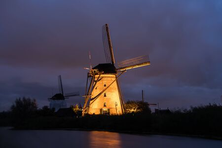 on the water there are several windmills in Kinderdijk in Holland Banco de Imagens