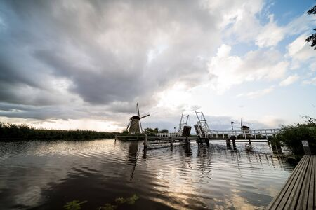 along the river there is a wooden drawbridge at a windmill from the kinderdijk