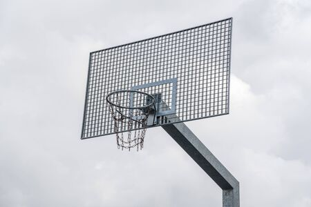 Metal basketball backboard with hoop and steel chains net in the park