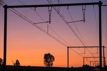 This track with electrical lines above runs in the distance of the landscape Stok Fotoğraf