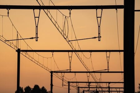 Electric overhead lines of a railroad train with a beautiful orange sunrise Stok Fotoğraf