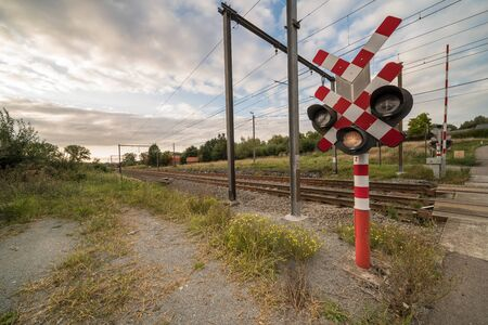 along the main lane of a busy road there is a railroad lights at a level crossing Stock fotó