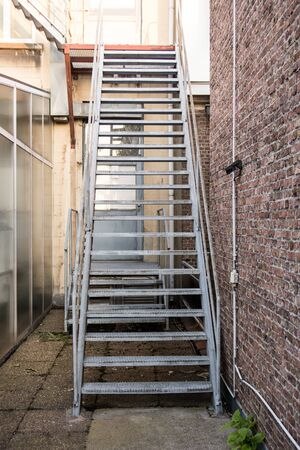 behind a building there is an iron emergency staircase to keep you safe in the event of a fire