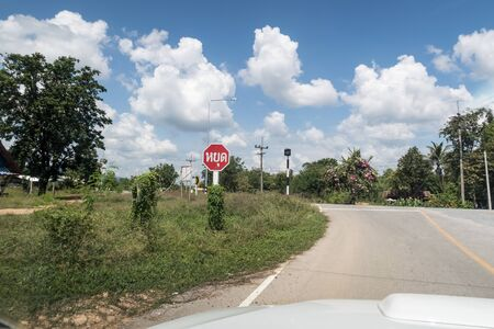 At the end of a road in Thailand there is a Thai stop sign with a thick line on the road