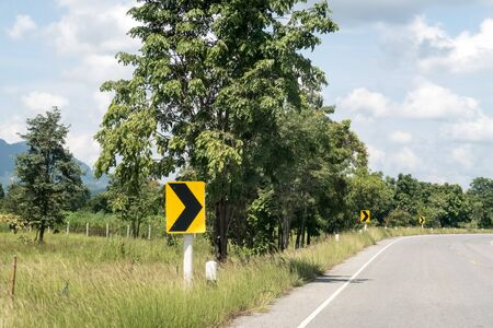 Yellow sign with curved arrow and road,Thailand