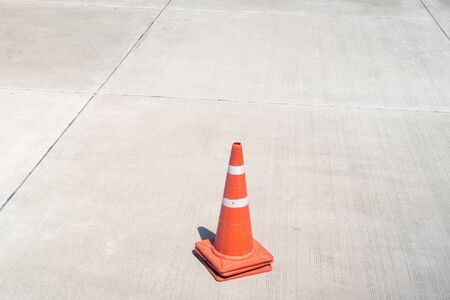 three traffic cones stacked together on the concrete roadway Stock fotó