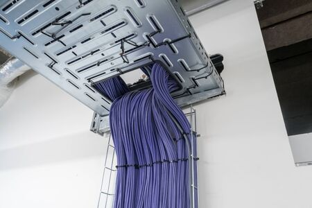 Electrical cables are located in a cableway on the roof of a building Stock Photo