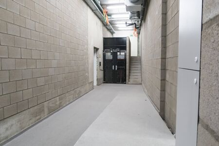 in a large building in the corridor there is a goods elevator next to a concrete staircase