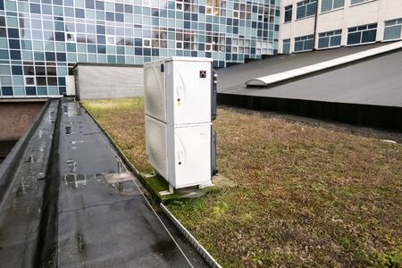 on a high building in the city there is cooling on a flat green roof Reklamní fotografie