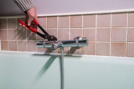 in the bathroom, the plumber is installing the thermostatic water tap