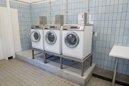 Three washing machines with coins are in a laundry Imagens