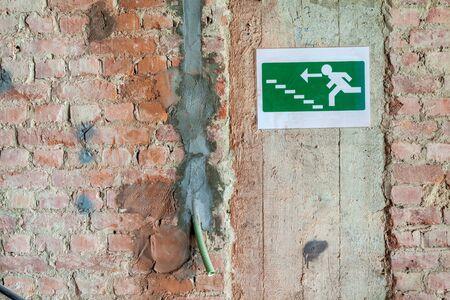 Se está renovando un antiguo edificio grande y hay un letrero de una ruta de escape en la pared Foto de archivo