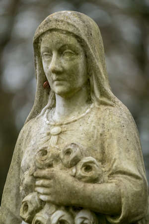 In an old cemetery there is a statue of a woman embedded in a marble top with some cobwebs.