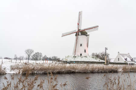 In the town of Damme not far from Bruges, this beautiful windmill stands along the river whit snow in the winter