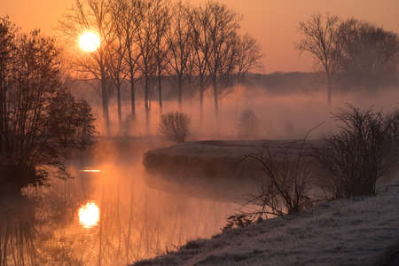 Early on a frosty morning with fog rising along a river with several bends Stock Photo