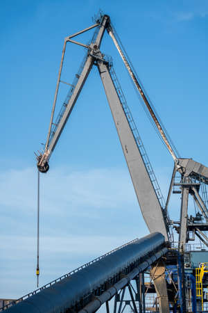 this old crane is located in the port area next to the water
