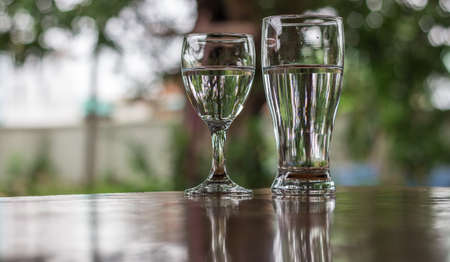 placed: Glass of water placed on a wooden table, Glass of water