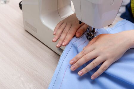 Close-up sewing machine, needle sews. The hand of a girl seamstress holds fabric