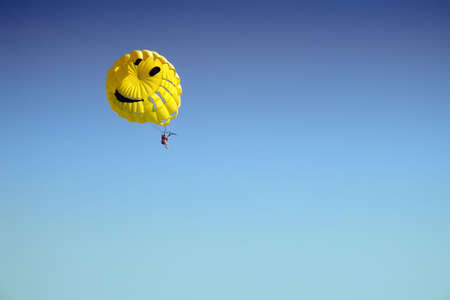 Yellow parachute high in the blue sky