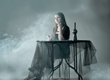 Woman sitting behind table in smoke