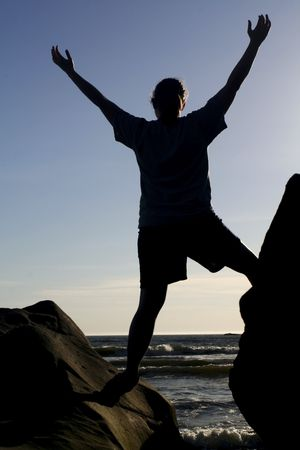 upraised: a silhouetted person  balancing on two rocks with arms raised Stock Photo