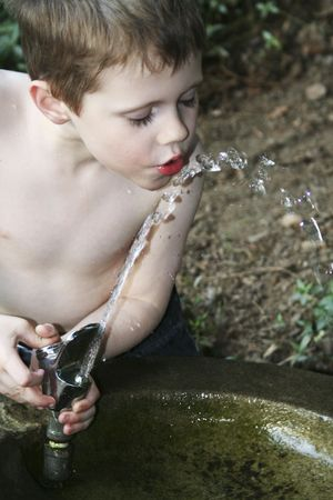 child playing in a water fountain photo
