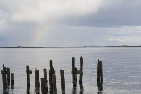 pilings: Rainbow and dock pilings after a storm Stock Photo