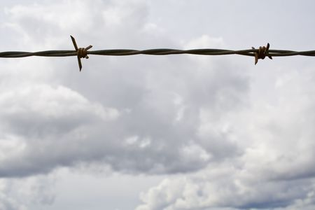 Barbed wire against a cloudy sky Stock Photo