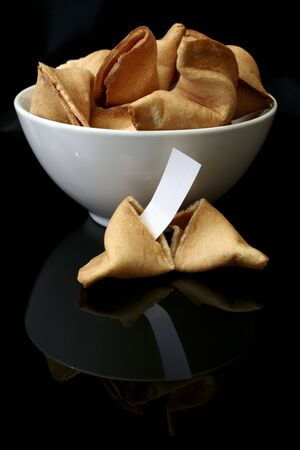 fortune cookies in a white bowl in a black background with one open cookie in front and a blank fortune photo