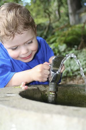 child playing with a water fountain