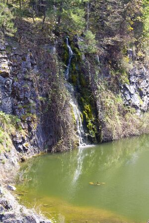 trickling: A waterfall trickling down a cliff into a lake
