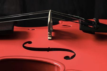 concerto: A close up of a red violin on a black background